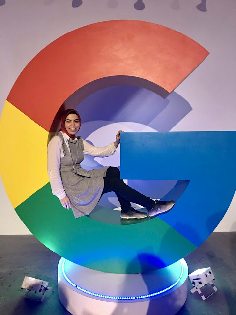 "Beyza sitting inside a giant ""G"" statue."