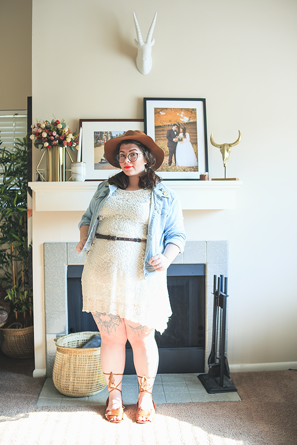 An outfit consisting of a brown panama hat, a denim jacket, a white lace dress with a brown belt, and brown lace up sandals.