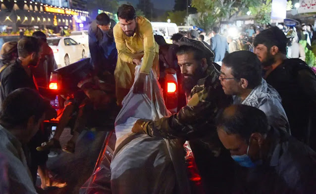 Volunteers and medical staff remove bodies from a pickup truck outside a hospital in the capital Kabul after two explosions. Photo: Getty