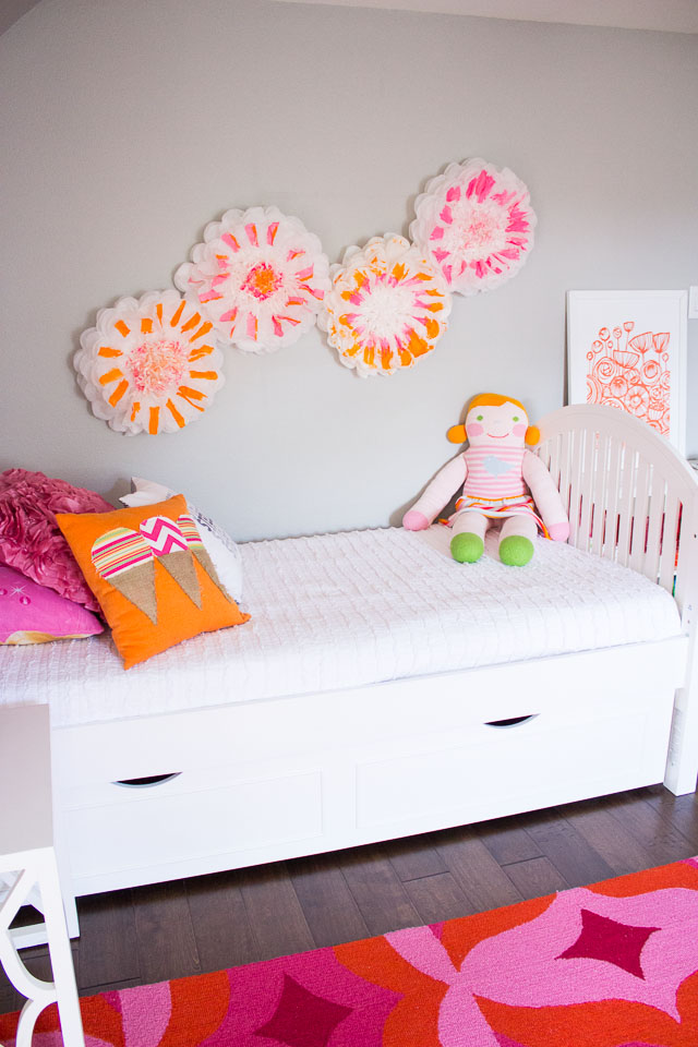 Tissue paper pom poms make for cute wall decor in kids bedrooms!