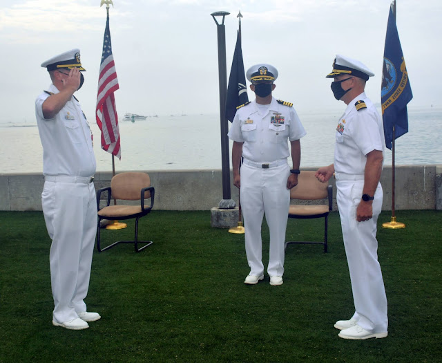 A Navy Captain salutes another Navy Captain. They are dressed in white uniforms on Naval Submarine Base Point Loma, California.