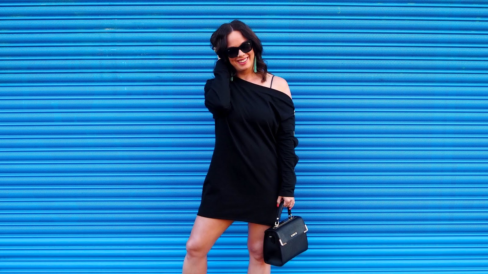 Black off-the-shoulder sweat dress with faux horn buttons on the sleeve