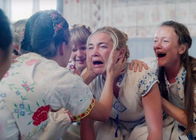 """ID: image shows a scene from the film """"Midsommar,"""" in which the main character, a young woman, Dani, is crying. Another women is across from her and holding Dani's face in her hands. Two women are behind Dani on either side, also crying and holding on to her from behind. They are dressed in vibrantly embroidered linens."""