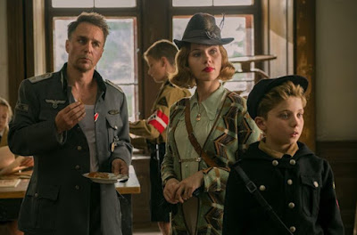 """Jojo Rabbit"" (2019) movie scene where Sam Rockwell, Scarlett Johansson, Roman Griffin Davis, and Alfie Allen stand in a Nazi headquarters"