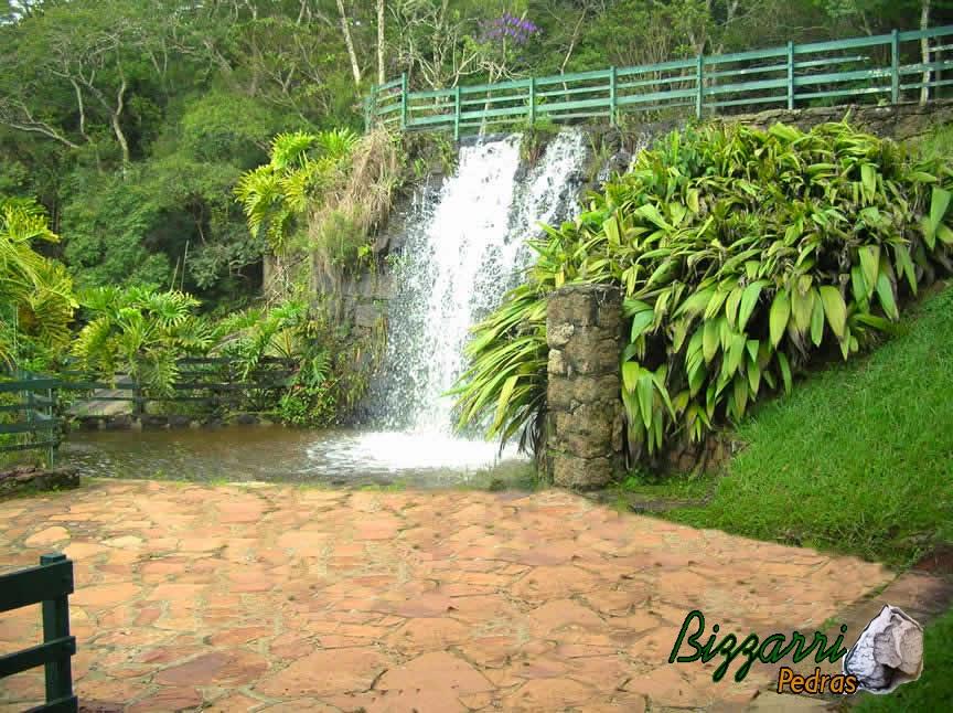Execução do calçamento de pedra cacão de São Carlos no piso junto a cascata de pedra com a construção da piscina natural, o muro de pedra e a execução do paisagismo em condomínio em Atibaia-SP.