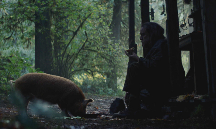 Imagem de capa: o personagem de Nicholas Cage, um homem barbudo em roupas usadas e gastas, um casaco com capuz, calças e botas, sentado na soleira de uma cabana ao lado de um porco numa floresta.