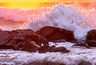 Close up of a wave splashing over rocks at sunrise - Ocean Grove, New Jersey