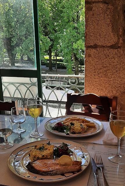 mesa de restaurante com pratos de comida e copos de vinho