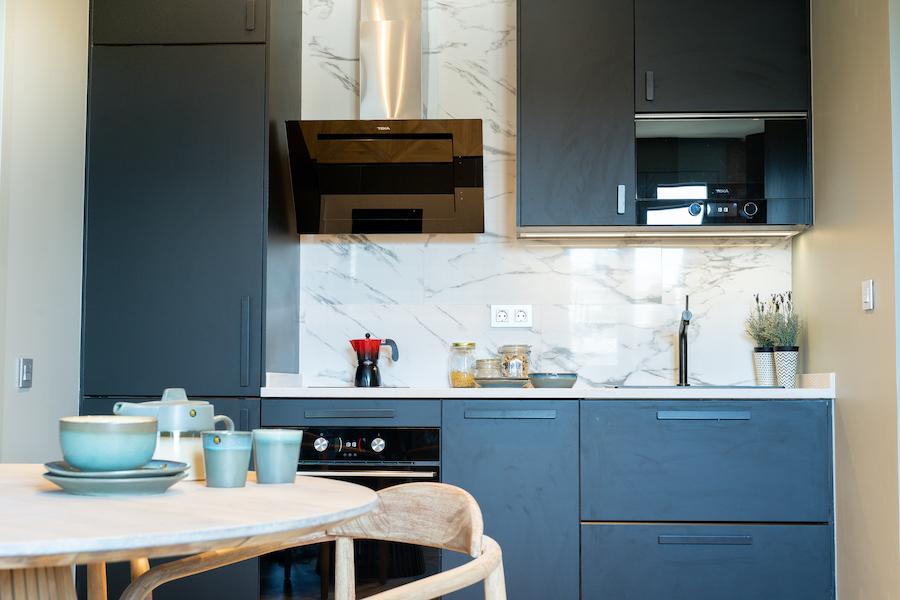 Cocina con electrodomésticos integrados, frente de madera azul y mármol blanco.