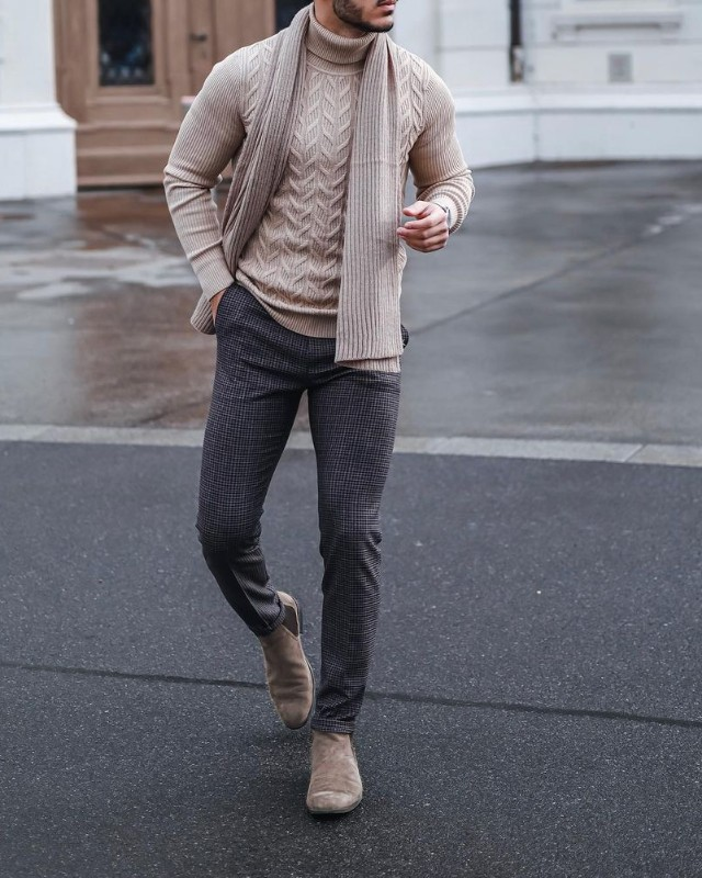 A man wearing Crew-neck sweater, woolen muffler, trousers and Chelsea boots attire.