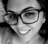Rosto de mulher, sorridente, usando óculos de armação preta.