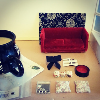 A mug of tea on a used envelope in a one-twelfth scale miniature room. Next to the mug is a card with a piece of blue and white japanese fabric on its front, a deep red miniature velvet sofa, a one-twelfth scale Yanagi butteryfly stool, three one-twelfth scale lucky cats, two one-twelfth scale cherry-blossom cushions, a pair of one-twelfth scale slippers and two pairs of one-twelfth scale chop sticks.