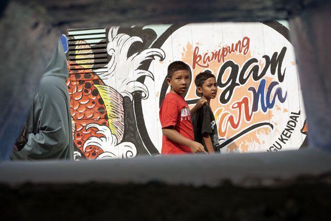 Anak-anak Kampung Mranggen melintasi mural-mural di kampungnya