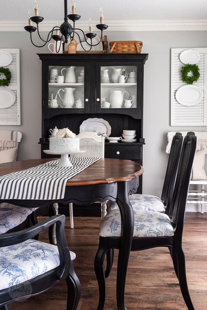 dining room with black hutch, white shutters, ironstone and striped table runner
