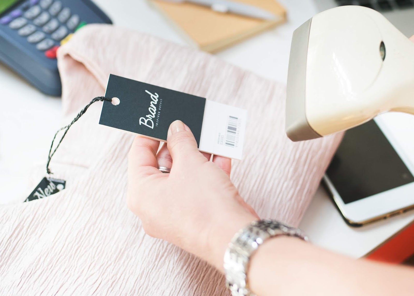 A cashier scanning a pink garment with a brand tag at a till