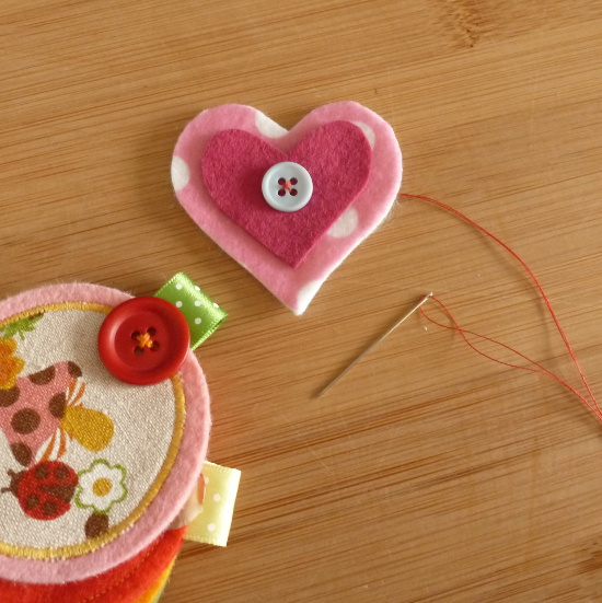 Sewing on buttons to fabric heart shapes