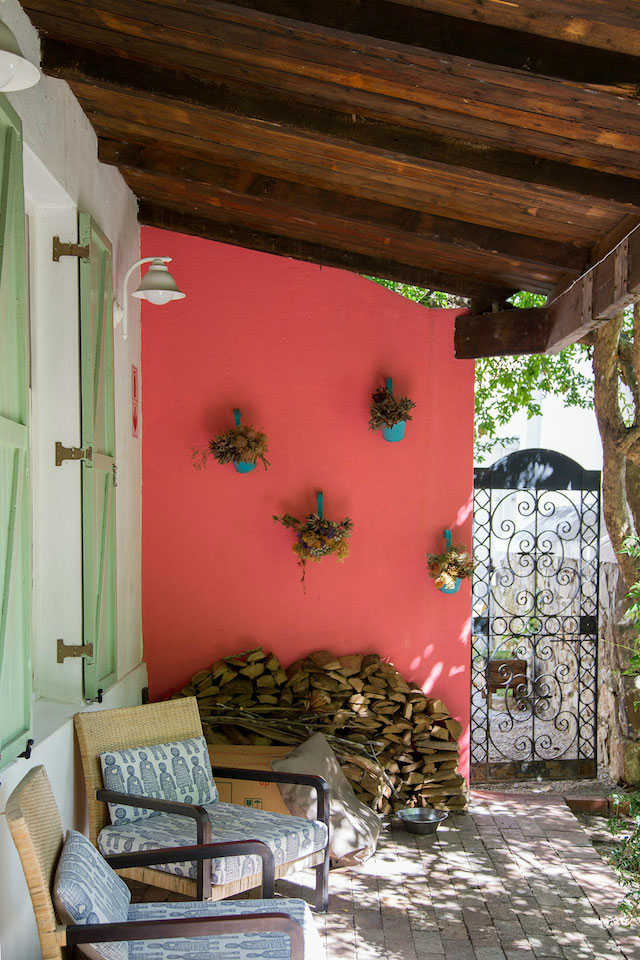 detalle del porche con pared roja, vigas de madera, contraventanas pintadas