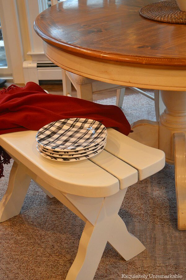 Curved white kitchen bench with plaid black dishes and a red throw