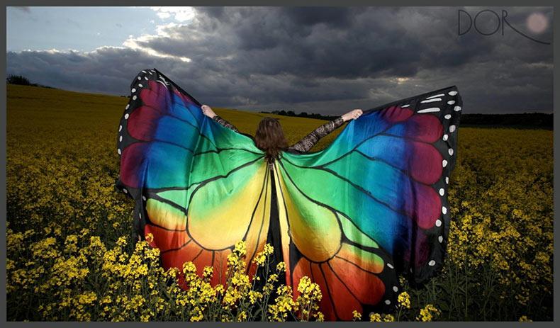 Alas de mariposa de seda pintados a mano fotografiados sobre artista en lugares maravillosos