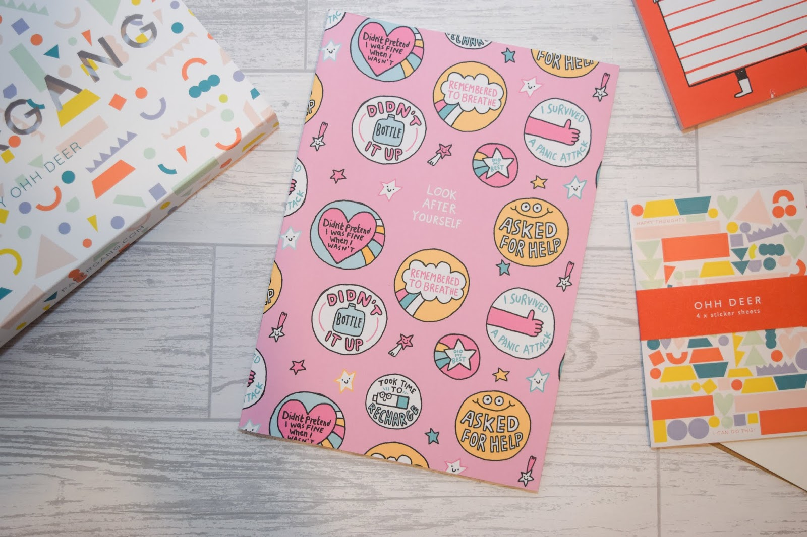 A pink notebook with self care reminders and quotes in circles printed all over the notebook. It is A4 and lying on a white wooden background.