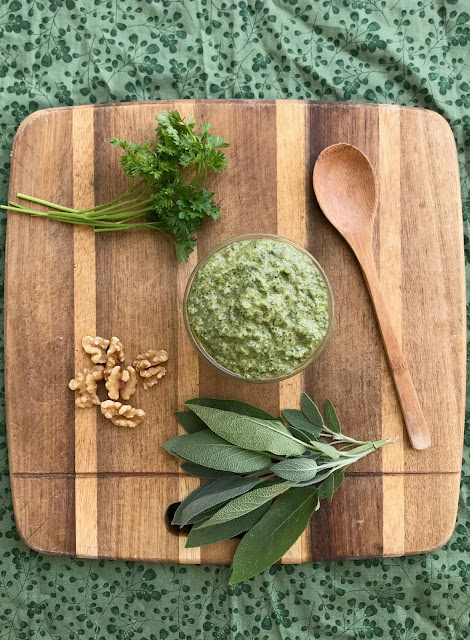 Top view of a jar of parsley and sage walnut pesto on a cutting board with herbs and walnuts.