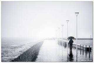 un hombre con un paraguas pasea junto al río Urumea y loscubos del Kursaal