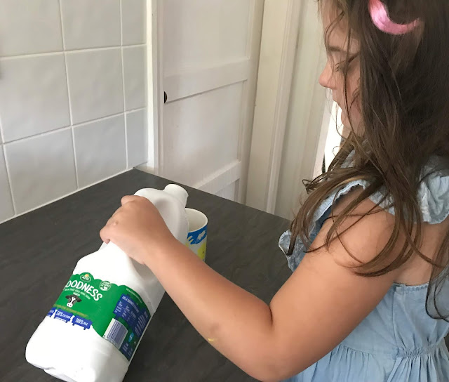 daughter poring a mug of Arla Goodness milk in the kitchen