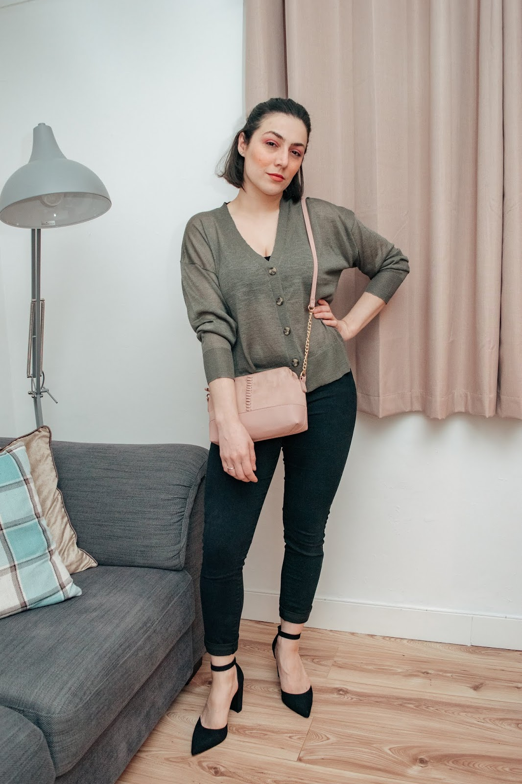 Standing wearing a khaki cardigan, black jeans and styling a pink cross body bag.