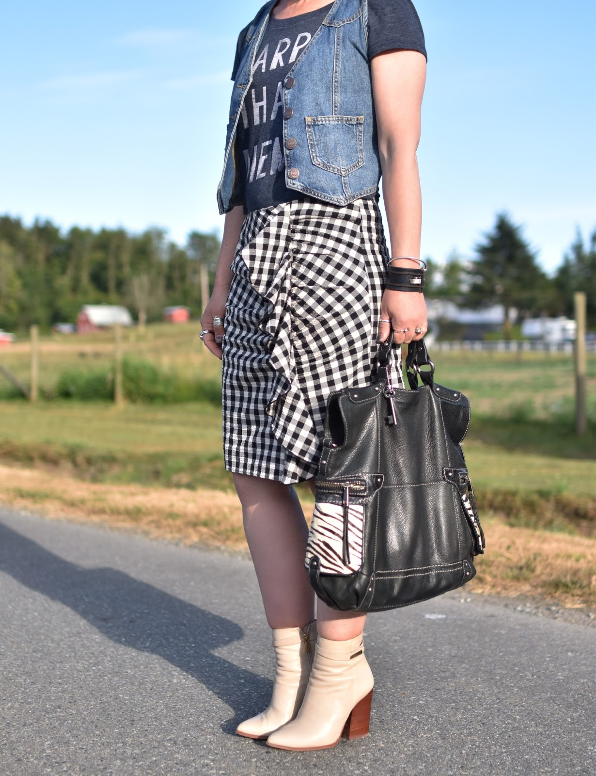 Monika Faulkner personal style inspiration - ruffled gingham skirt, graphic tee, denim vest, ivory booties, Fossil bag