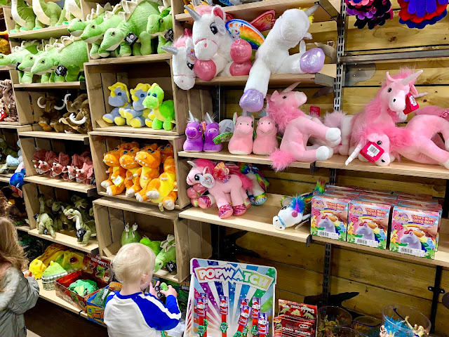 A toddler in a toy shop looking at soft animals