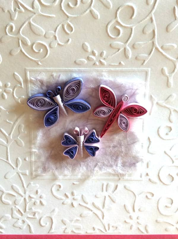 close-up van drie quilled vlinders op kaart met bloemenreliëf