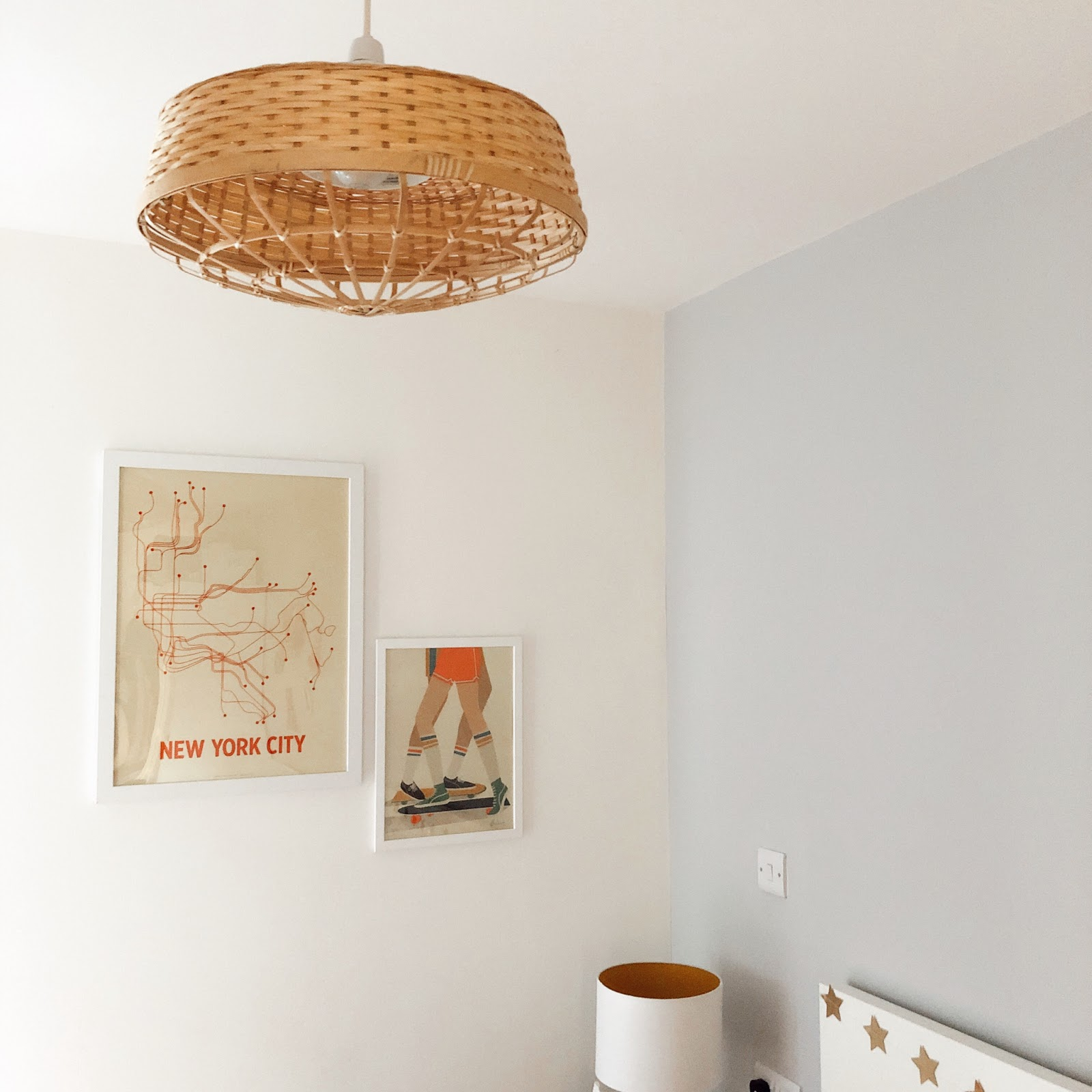 corner of bedroom with pink patterned bedsheets, rattan lampshade, orange prints and side table with mid century lamp
