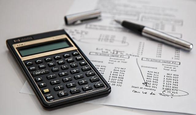 calculadora, planilhas e canetas sobre a mesa