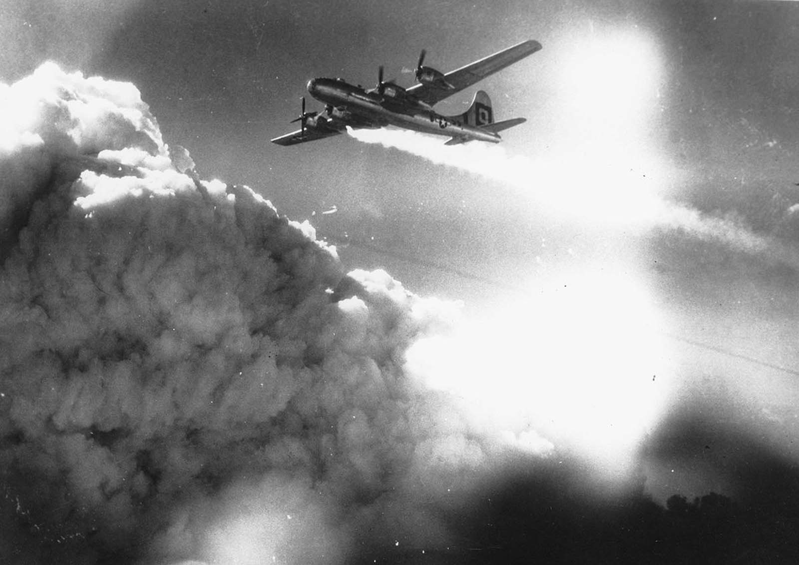 In flight over the Japanese city of Kobe, a U.S. Army Air Forces B-29 Superfortress trails smoke and fire, on July 17, 1945.