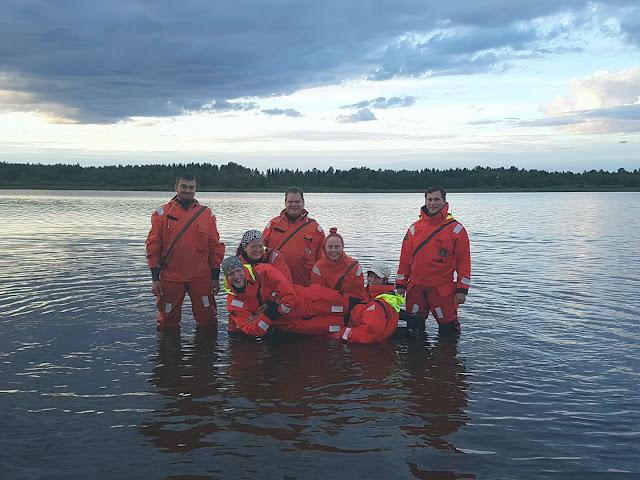 7 henkeä poseeraa polvensyvyisessä vedessä pelastautumispuvut päällä