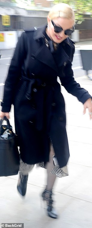 Madonna steps out in a conservative trench coat as she headed out in London's Portman