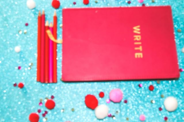 Pink notebook that says write placed on top of blue glitter background