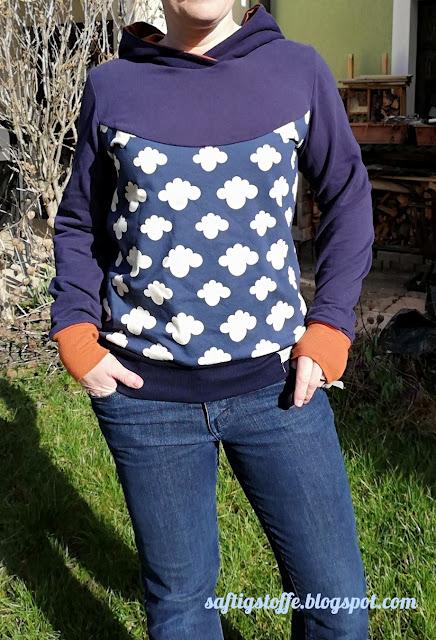 blauer Hoodie mit Wölkchen-Muster und orange-farbener Kapuze angezogen.
