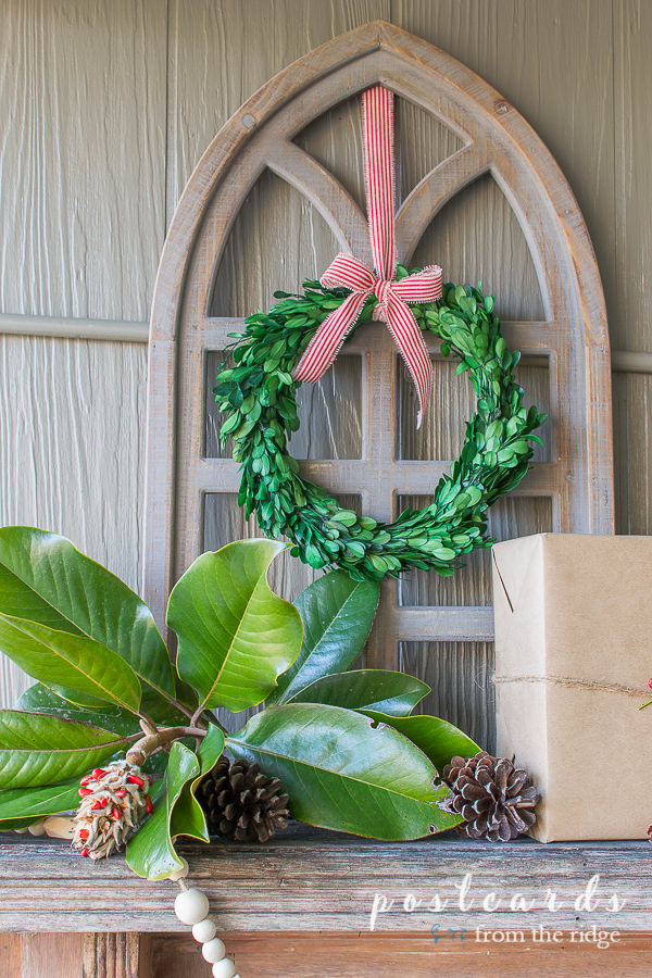 preserved boxwood wreath and magnolia leaves with wood cathedral window frame