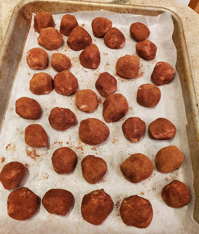 This is a pan of Irish Potato Candy rolled in cinnamon on a cookie sheet no bake recipe