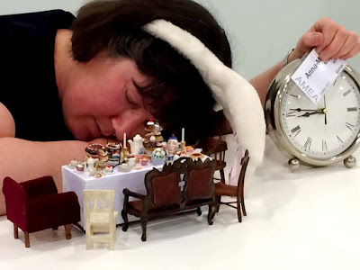 Woman wearing rabbit ears, asleep in front of a dolls' house miniature table set for tea, holding a large clock.