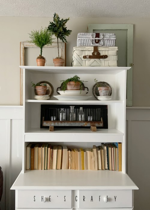 Spring Home Tour - living room white book shelf with topiaries and dish stacks.