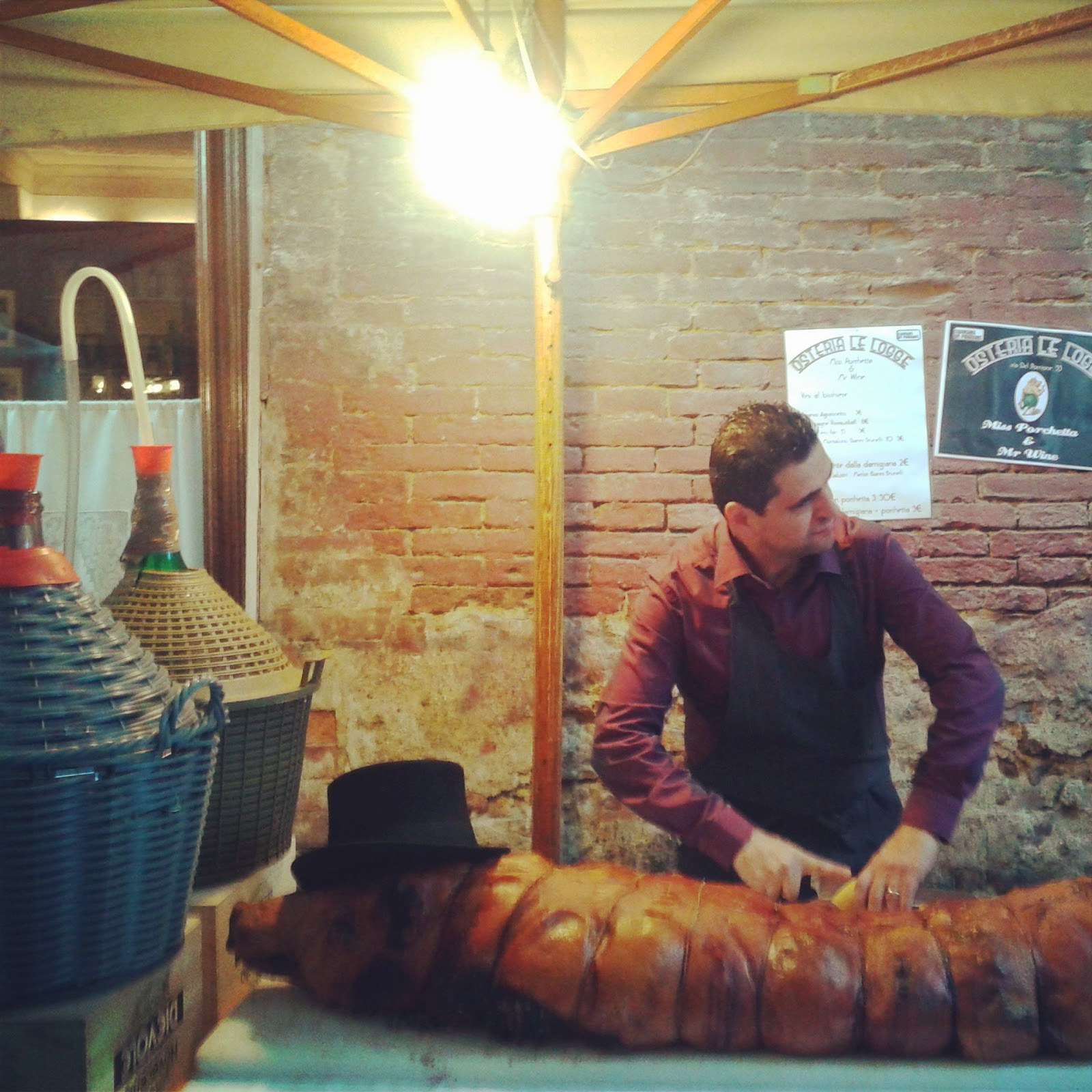 Mirco from restaurant le Logge cutting up Porchetta in front of Le Logge during a street festival