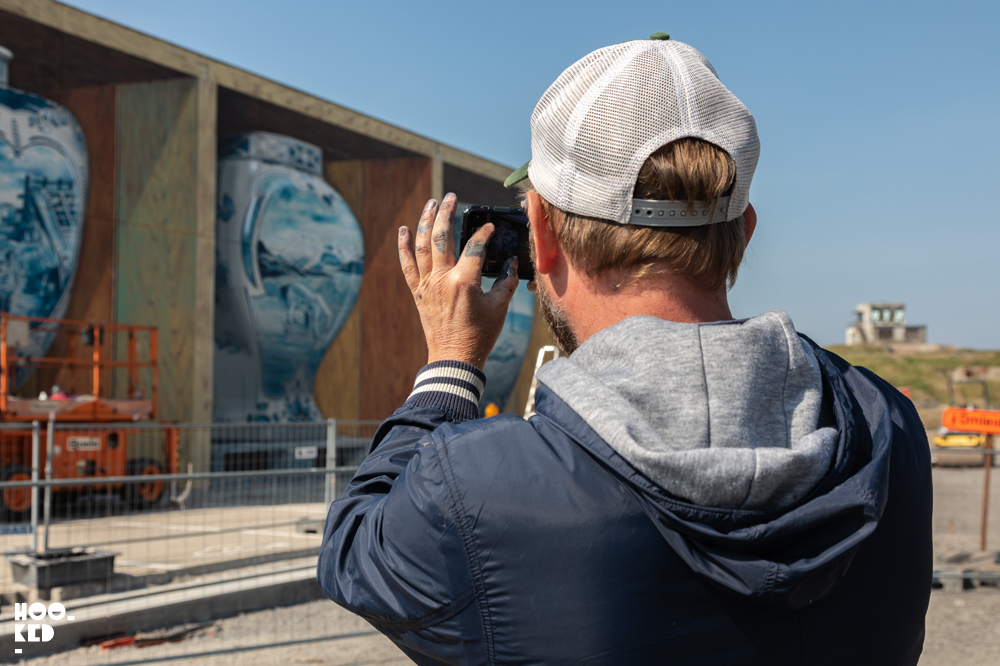Leon Keer check the perspective of his 3d mural on his phone