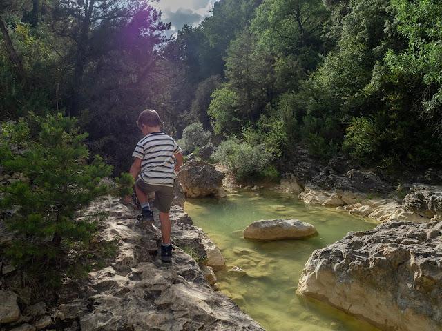 Niño de espaldas con el sol detrás caminando junto a una de as pozas de San Martín (Huesca)