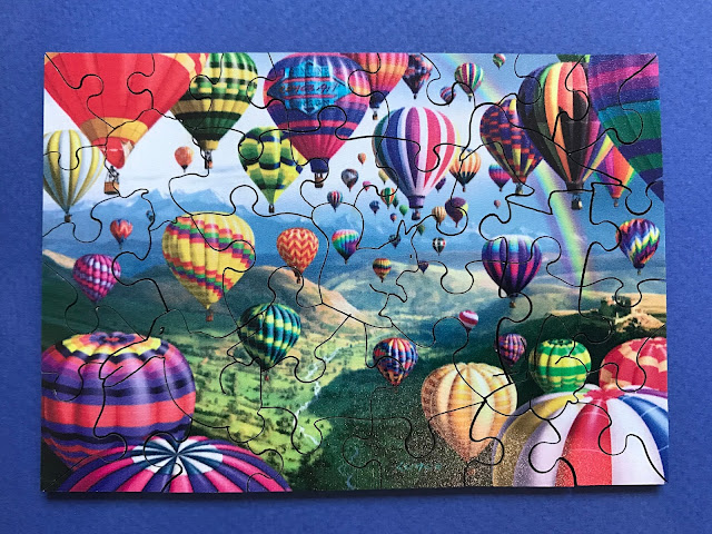 A wentworth wooden jigsaw puzzle with hot air balloons on. Some of the pieces are interest shapes like a squirrel and a bird