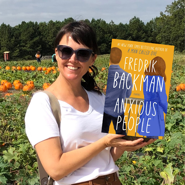woman holding a book in a pumpkin patch