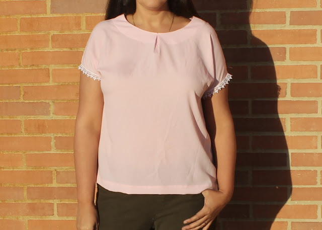 A woman wearing a pink crepe top with lace-trimmed sleeves made from the Avid Seamstress Drop-Sleeved Top sewing pattern.