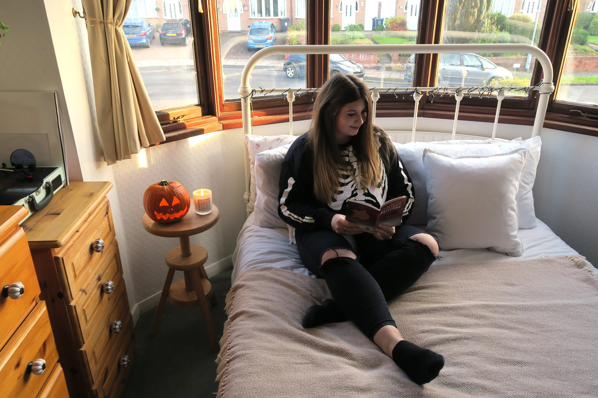 Grace is sitting on her bed reading a book titled 'ghost stories'. She is wearing a black jumper with a skeleton on it and beside her is a carved pumpkin.