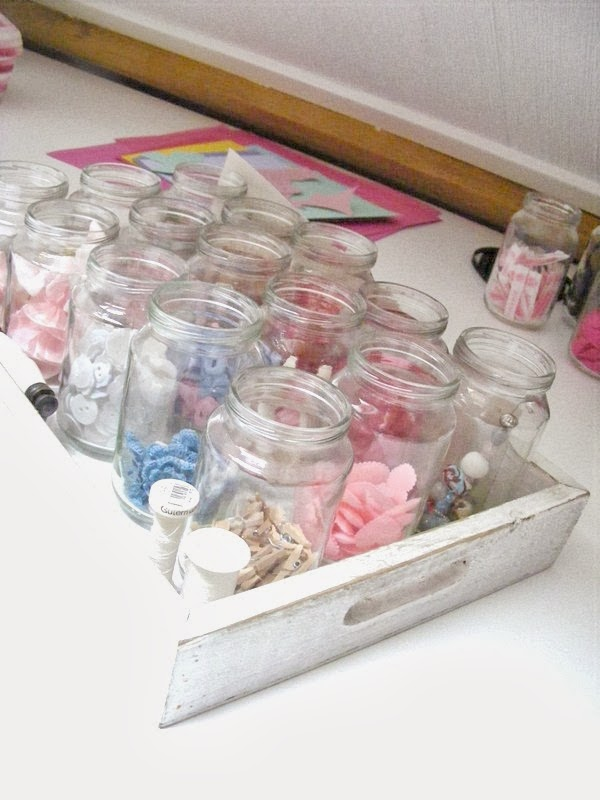 A tray of jars full of craft notions, buttons and ribbons